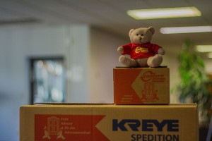 Das Bild zeigt Umzugskartons der Spedition Kreye und einen Stoffteddybären